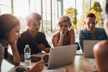 amigos de la universidad de socialización y estudian juntos. Grupo de estudiantes que se sientan a la mesa en la biblioteca y el uso de ordenador portátil.