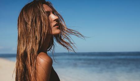 해변에서 아름다운 젊은 여자의 초상화를 닫습니다. 바다 해안에 젊은 백인 여성 모델입니다.