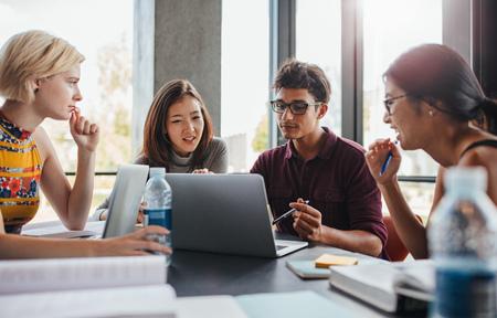 Multikulturelle junge Leute am Tisch tun Gruppe Studie. Studenten der Universität sitzen am Tisch zusammen mit Bücher und Laptop für die Informationen für ihr Projekt zu erforschen.