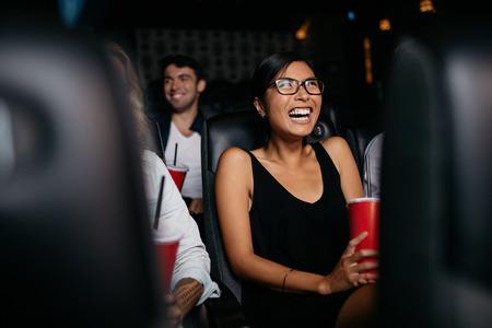 멀티 플렉스 영화 극장보고 영화에 앉아 웃 고 젊은 여자의 총. 스톡 콘텐츠