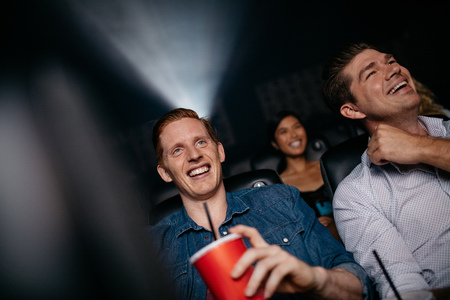 comedic: Young men watching movie in cinema. People in theater with drinks watching film.