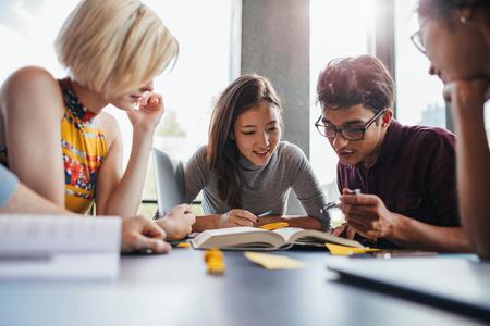 라이브러리에서 학교 지정 작업 젊은 학생들의 그룹입니다. 다민족적인 젊은 사람들이 공부를 위해 참고 도서를 읽는 테이블에 앉아.