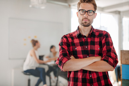 designer working: Portrait of confident young entrepreneur standing in office with coworkers meeting in background.