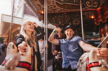 Aufnahme von jungen Leuten auf einer Fahrt im Vergnügungspark, die Spaß haben. Lächelnder Mann und Frau auf Pferdekarussellfahrt auf dem Rummelplatz. Standard-Bild