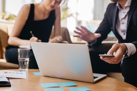 Foto de compañeros de trabajo trabajando juntos en la computadora portátil en la oficina. Hombre que sostiene el teléfono móvil y la mujer escribiendo notas.