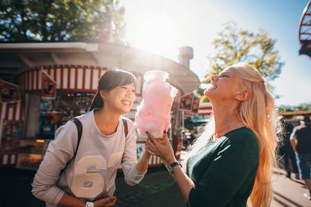 Shot van gelukkige vrouwelijke vrienden in pretpark suikerspin eten. Twee jonge vrouwen genieten van een dag in het pretpark. Stockfoto