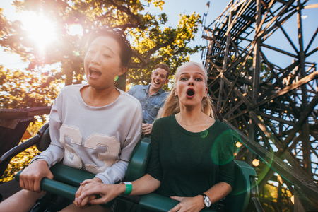 Shot of young friends enjoying riding roller coaster at amusement park. Young people having fun on rollercoaster. Zdjęcie Seryjne