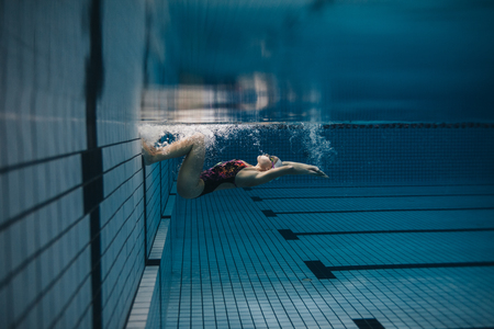Shot of fit young woman turning over underwater. Female swimmer in action inside swimming pool. 스톡 콘텐츠