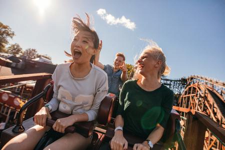 Jeunes amis sur des montagnes russes palpitantes. Jeunes femmes et hommes s'amusant au parc d'attractions. Banque d'images