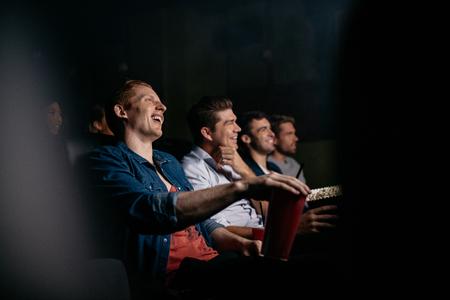 Grupo de amigos sentados en el cine multiplex. Jóvenes viendo películas en la sala de cine y sonriendo.