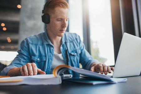 Innenaufnahme eines männlichen Studenten, der in der Bibliothek der Universität studiert. Junger Mann mit Laptop und Lesebuch mit Fokus an Hand. Standard-Bild