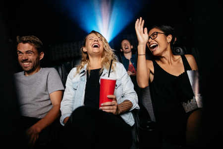 Group of people in theater with popcorn and drinks watching movie and laughing. Young women and men watching comedy movie in cinema. Imagens