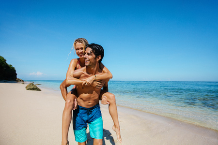 Portrait of happy young couple piggyback on tropical beach. Man carrying girlfriend on his back along the sea shore.