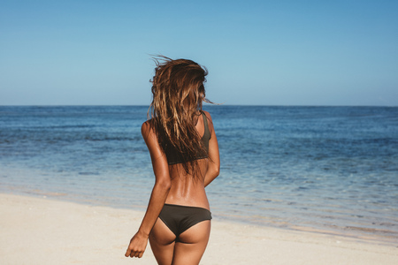 Rear view of young woman in bikini running on the beach. Caucasian female model on the sea shore.