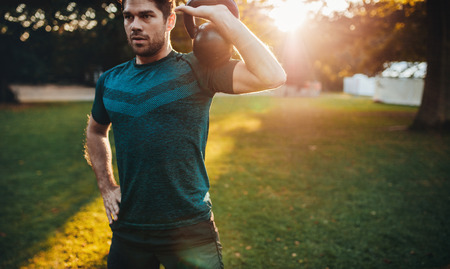 Shot of healthy young man working out with kettlebell. Fitness male model training at park in morning.