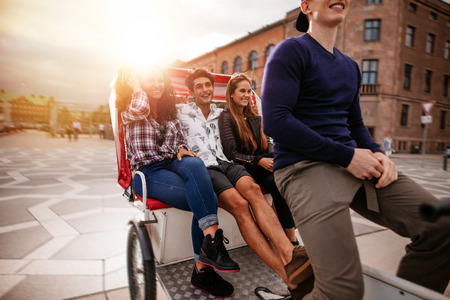 Teenage friends enjoying tricycle ride. Teenagers riding on tricycle in city and having fun.
