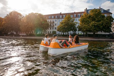 Aufnahme von Freunden im Teenageralter, die sich auf dem Tretboot im See entspannen. Junge Männer und Frauen, die Boot fahren und Ferien genießen.