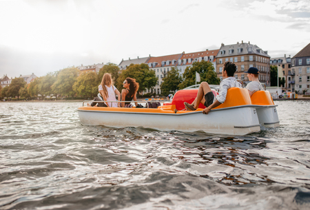 Outdoors shot of teenage friends sitting in pedal boat. Group of people enjoying boating in the lake. Stock Photo