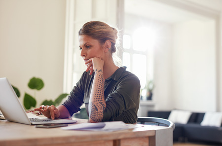 home office: Portrait of beautiful young woman sitting at home office using laptop. Female looking busy working on laptop. Stock Photo