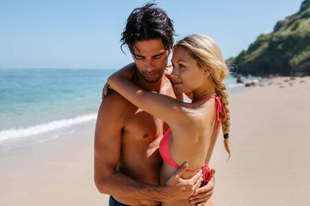 Portrait of romantic young couple embracing on the beach. Beautiful young woman in bikini with her boyfriend on the sea shore enjoying summer holidays.
