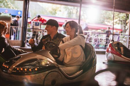 dashing: Friends on bumper car ride in amusement park. Young man and woman having fun with bumper cars at fairground.
