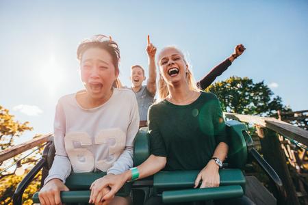 Enthousiaste jonge vrienden rijden achtbaan bij pretpark. Jonge mensen die pret bij pretpark.