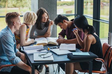 Los jóvenes sentados en la mesa de trabajo sobre la asignación de escuela. Grupo multirracial de estudiantes que estudian juntos en una biblioteca.