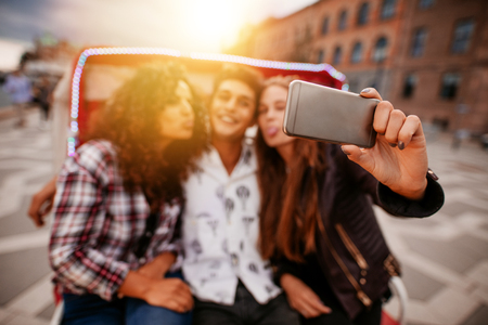 rickshaw: Young woman taking selfie on tricycle with friends. Young man and women riding on tricycle bike and taking self portrait. Focus on smart phone. Stock Photo