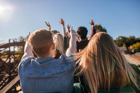 Вид сзади выстрел из молодых людей на захватывающее американских горках в парке аттракционов. Группа друзей, с удовольствием на ярмарке и наслаждаясь на поездке.