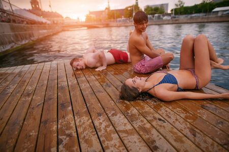 young friends: Shot of young people relaxing on jetty. Happy teenage friends relaxing on pier over lake. Stock Photo