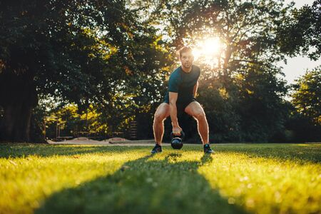 sportsperson: Full length portrait of fitness young man training with kettlebell in the park. Fit caucasian model doing physical workout in the park.