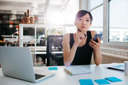 携帯電話を持つ彼女の机に座って自信を持ってアジア女性の肖像画。オフィスで働くアジアの実業家。