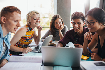 Wielorasowe grupy młodych studentów studiujących w bibliotece. M? Odzi ludzie siedz? Razem przy stole z ksi ?? ek i laptopa w celu zbadania informacji dla ich projektu. Zdjęcie Seryjne