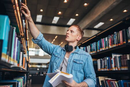 finding: Shot of young male student selecting book from library shelf. University student studying in library.