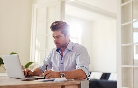 hombre escribiendo: tiro bajo techo de hombre joven que trabaja en la computadora portátil en la oficina y escribir notas. hombre de negocios que trabaja desde su casa.