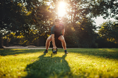 Shot of fit young man exercising with kettlebell outdoors in the park.  Strong young guy training at park in morning. Stock Photo