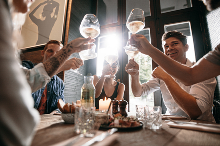 Group of young people making a toast at restaurant. Men and women sitting at a table in cafe and toasting wine.