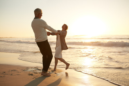 로맨틱 한 고위 커플 해변에서 하루를 즐기고의 전체 길이 쐈 어. 해변에서 그들의 휴가를 즐기는 성숙한 커플.