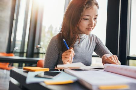 Libro de lectura asiático joven de la mujer en biblioteca de la universidad. Estudiante femenina preparando para exámenes finales. Foto de archivo