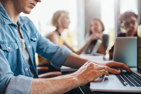 Ciérrese encima del tiro del hombre joven que usa la computadora portátil con los compañeros de clase que estudian en fondo. Estudiantes que aprenden en la biblioteca de la universidad. Foto de archivo
