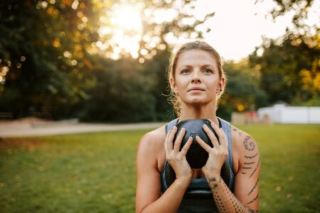 sportsperson: Portrait of fit young woman doing workout with kettlebell. Fit and muscular woman exercising in park.