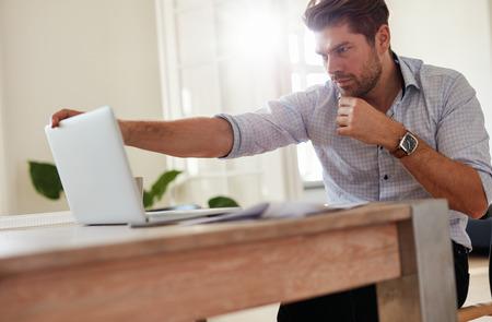 Tiro del hombre de negocios joven que se sienta en la tabla con la computadora portátil. Hombre caucásico que trabaja en la computadora portátil.