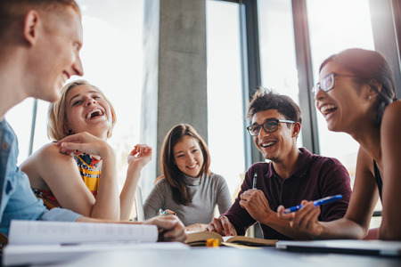다민족적인 젊은 사람들이 테이블에 앉아 함께 시험을 위해 공부하는 동안 재미. 라이브러리에서 행복 한 젊은 학생들의 그룹입니다.