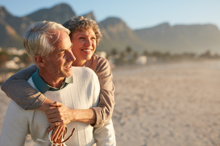 Portrait of happy mature man carrying his beautiful wife on his back at the beach. Senior couple enjoying their vacation at the sea shore. Фото со стока