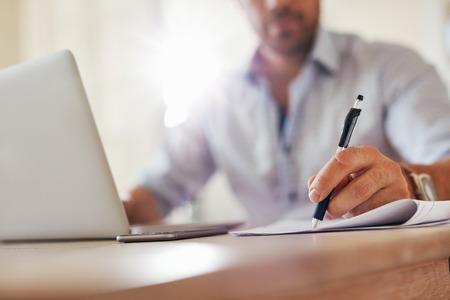 Zblízka zastřelil mladých obchodních mužů rukou s perem psaní poznámek na papíře. Mužský výkonný posezení u stolu u domácí kanceláře.
