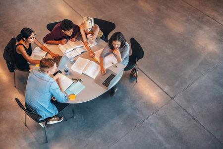 一緒に学ぶ若い学生の多民族のグループ。若い人たちのテーブルに座って、パソコンの勉強のハイアングル撮影。