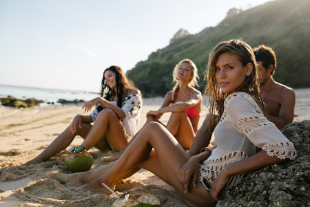 放松在与她的朋友的海滩的美丽的少妇在背景中。小组海滩假日的朋友。