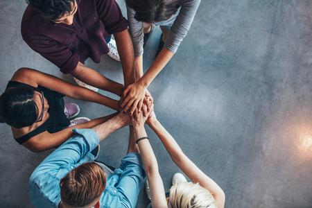 manos: Vista superior de los jóvenes poniendo sus manos en la parte superior de uno al otro. Los jóvenes estudiantes que hacen una pila de manos con espacio de copia.