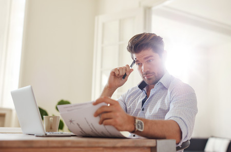 Shot of a young man sitting at table looking at documents and thinking. Business man going through paperwork at home office. Stock Photo
