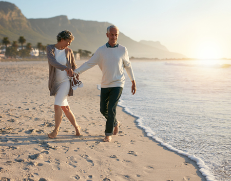 leisurely: Senior couple walking leisurely on the beach while holding hands. Enjoying summer vacation on the beach.